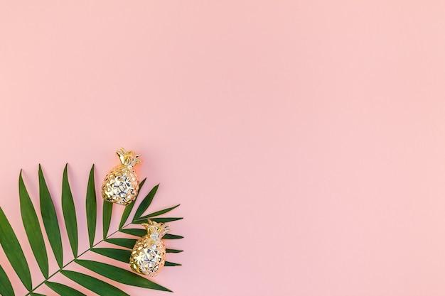 Vista superior plana e criativa de folhas de palmeira tropical verde com fundo de papel rosa milenar com espaço de cópia de abacaxis