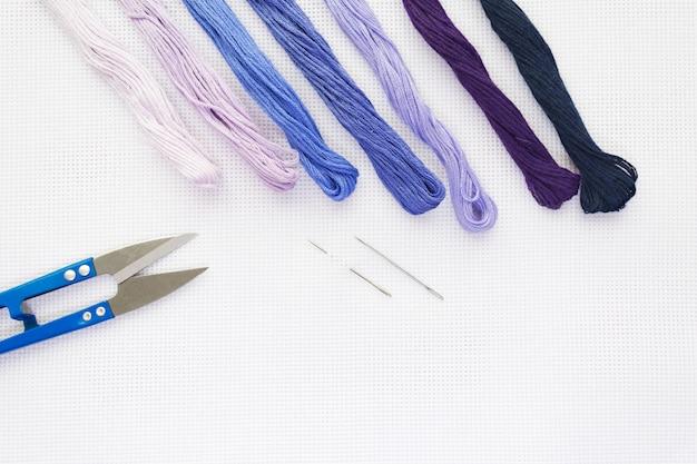 Vista superior plana leiga com uma tela de bordado, agulhas, tópicos em coloues azuis