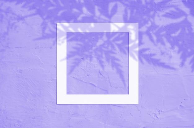 Vista superior plana leiga de copyspace criativo com moldura de papel e sombra de palma de folhas tropicais sobre fundo de cor violeta.
