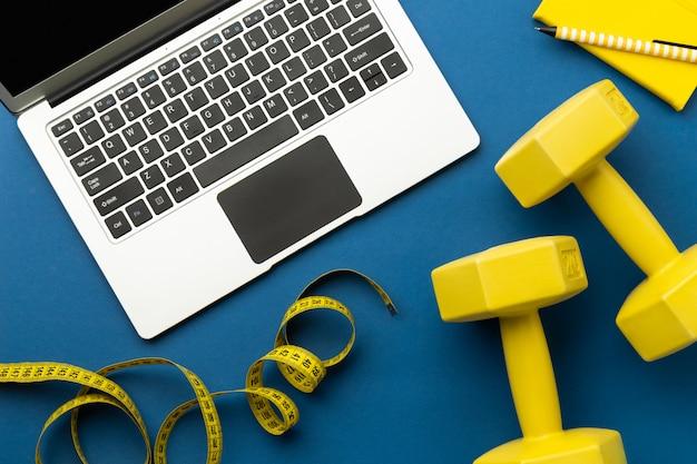 Vista superior plana leiga do laptop com equipamentos de esporte amarelo sobre fundo azul clássico