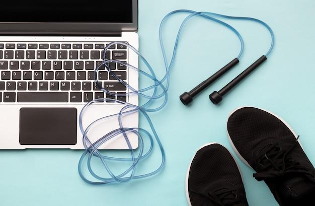 Vista superior plana leiga do laptop com equipamentos de esporte em fundo azul.