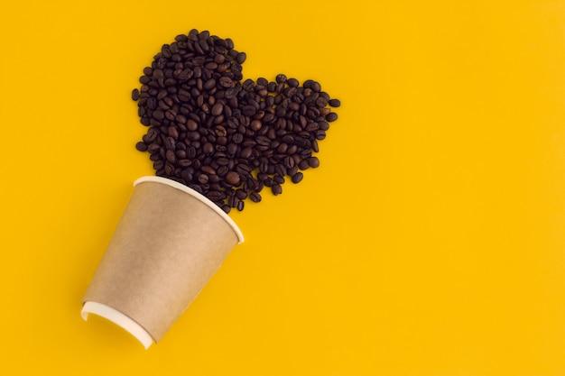 Vista superior plana leigos copo de papel café com coração feito de grãos de café, isolados em um amarelo