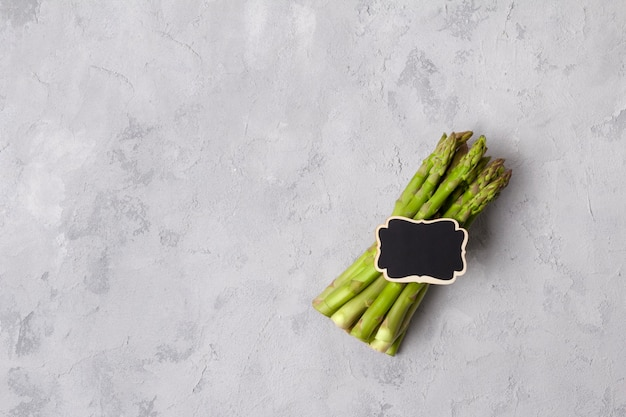 Vista superior plana leigos de espargos verdes frescos na mesa de concreto cinza