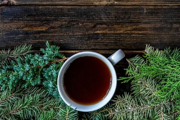 Vista superior plana leigos xícara de chá perto de galhos de pinheiro numa superfície de madeira.