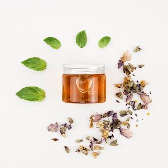 Vista superior pote de mel com folhas e flores ao redor