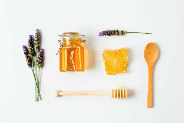 Vista superior pote de mel com lavanda e colheres