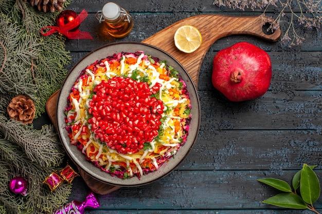 Vista superior prato de natal prato de natal e limão no quadro ao lado da garrafa de óleo de romã e ramos de abeto com brinquedos para árvores de natal