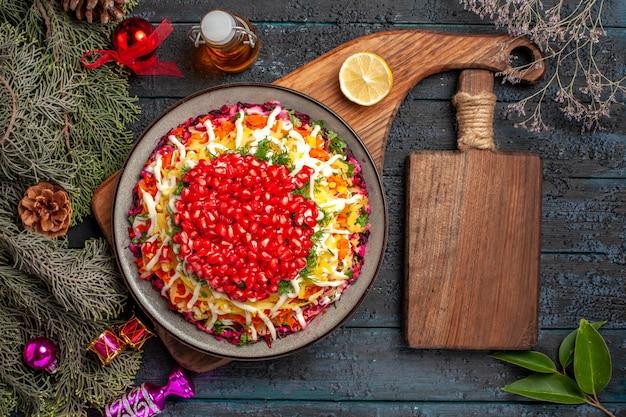 Vista superior prato de natal prato de natal no quadro ao lado do quadro da cozinha, garrafa de óleo e ramos de abeto com brinquedos para árvores de natal