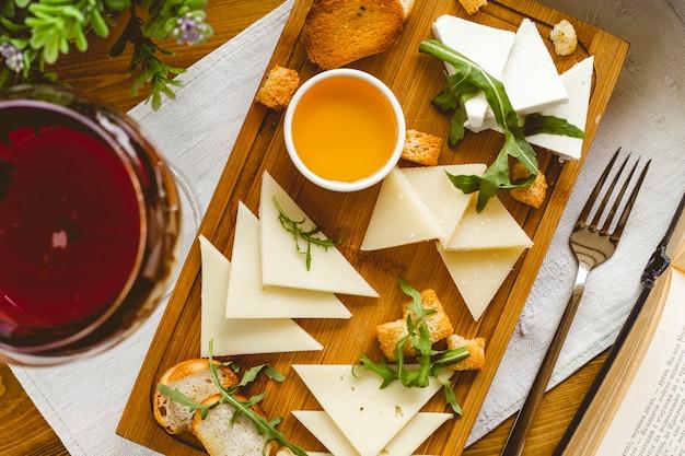 Vista superior, prato de queijo, uma variedade de queijos com rúcula de mel e bolachas no quadro
