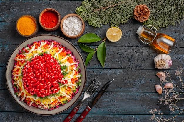 Vista superior prato prato de natal garrafa de alho óleo ao lado de tigelas de garfo e faca de diferentes especiarias ramos de abeto de limão com cones na mesa
