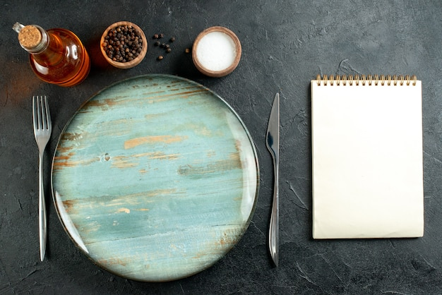 Vista superior, prato redondo, faca e garfo, pimenta preta e caderno de garrafa de óleo de sal na mesa preta