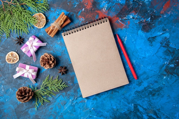Vista superior presentes de natal abeto galhos de árvore cones anis caderno lápis na superfície azul