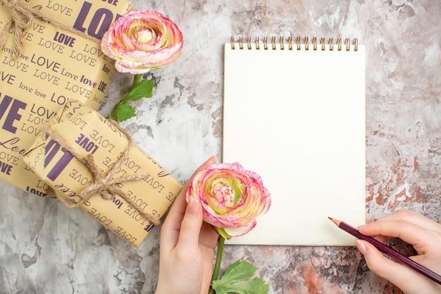 Vista superior - presentes fofos em pacote com flores na superfície clara