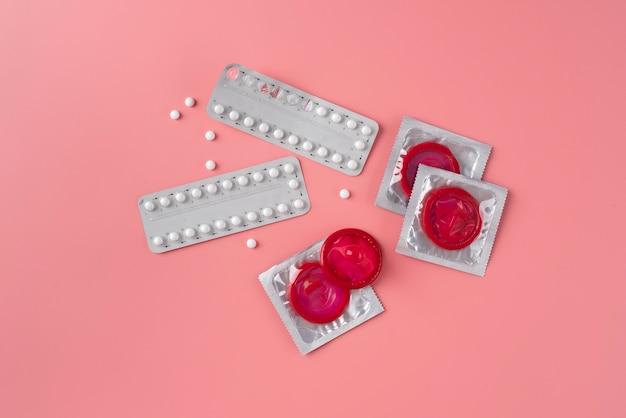 Vista superior preservativos e pílulas vermelhos