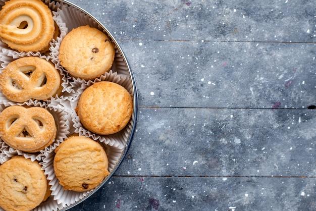 Vista superior próxima de biscoitos doces deliciosos diferentes formados dentro da embalagem redonda em cinza