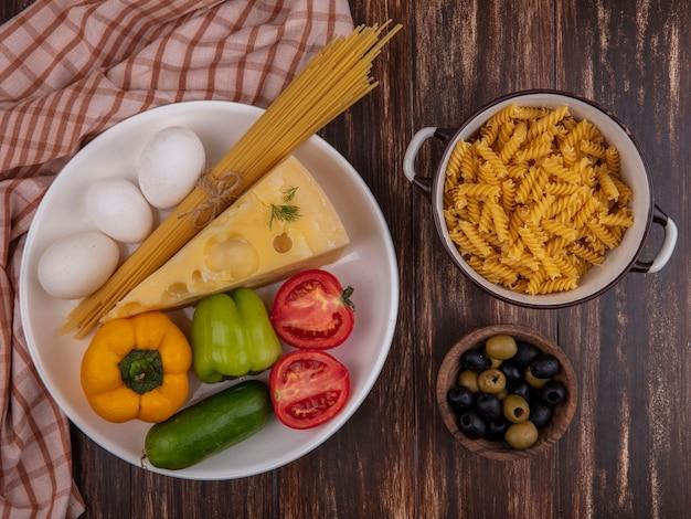 Vista superior queijo maasdam com frango ovos tomate pepino espaguete cru e pimentão em um prato e macarrão cru em uma panela sobre um fundo de madeira