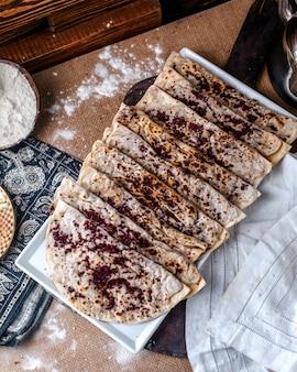 Vista superior qutabs famosa refeição de carne oriental com carne picada dentro e com tempero marrom chamado sumax dentro de chapa branca na superfície marrom
