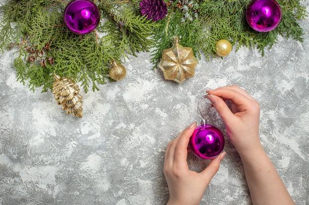 Vista superior ramos de abeto enfeites de árvore de natal bola de natal na mão da mulher em fundo cinza