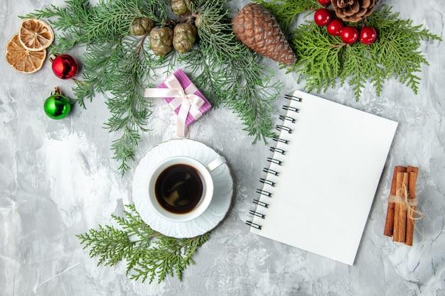 Vista superior ramos de pinheiro xícara de chá pequenos presentes brinquedos da árvore de natal caderno canela na superfície cinza