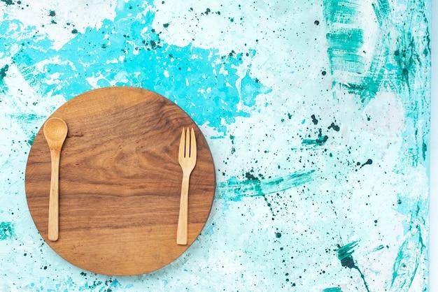 Vista superior redonda da mesa de madeira de cor marrom com um garfo de colher de madeira no fundo azul claro.