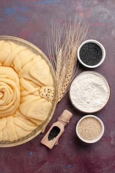 Vista superior redonda de torta crua formada com temperos na mesa roxa