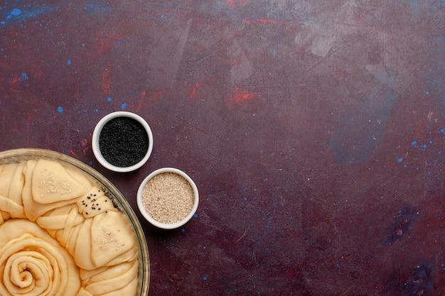Vista superior redonda de torta crua formada na superfície escura