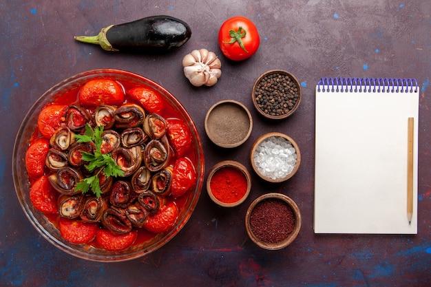 Vista superior refeição de vegetais cozidos, tomates e berinjelas com temperos na superfície escura