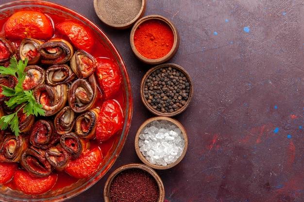 Vista superior refeição de vegetais cozidos, tomates e berinjelas enrolados e cozidos com temperos na mesa escura