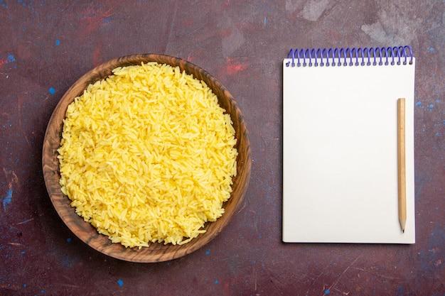 Vista superior refeição deliciosa de arroz cozido dentro de um prato marrom no espaço escuro