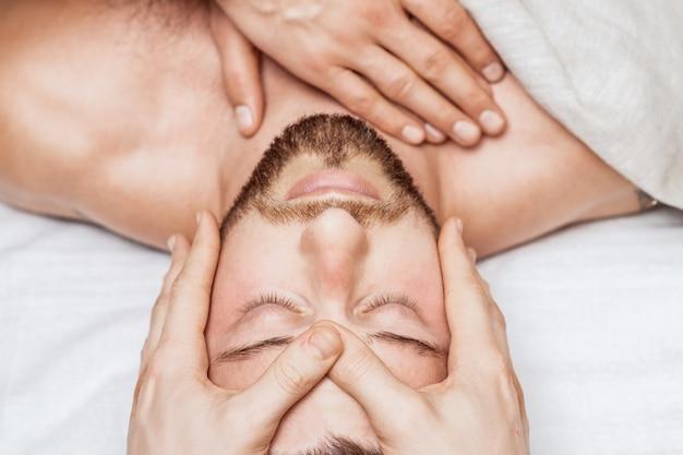 Vista superior relaxante de um jovem caucasiano desfrutando de uma massagem na cabeça por dois massagistas
