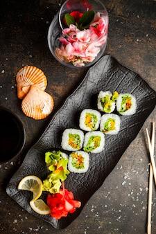 Vista superior rolo conjunto com gengibre em conserva e wasabi e molho de soja e pauzinhos no prato escuro