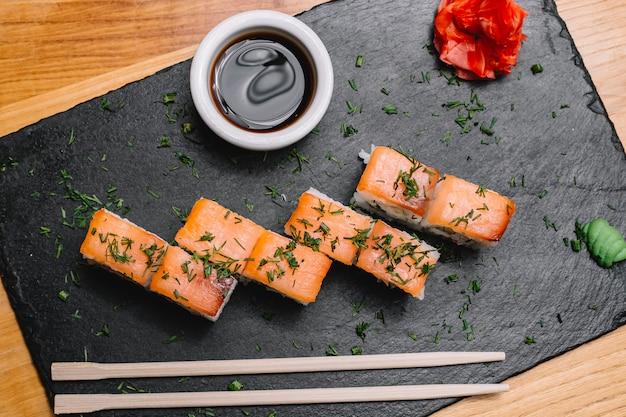 Vista superior rolo de filadélfia com salmão defumado creme de queijo pepino gengibre wasabi e molho de soja em uma placa