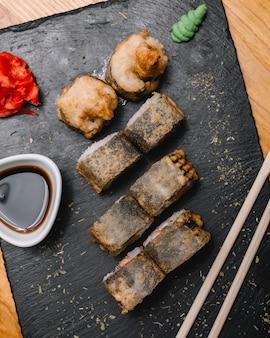 Vista superior rolo quente com pauzinhos de gengibre wasabi e molho de soja em uma placa