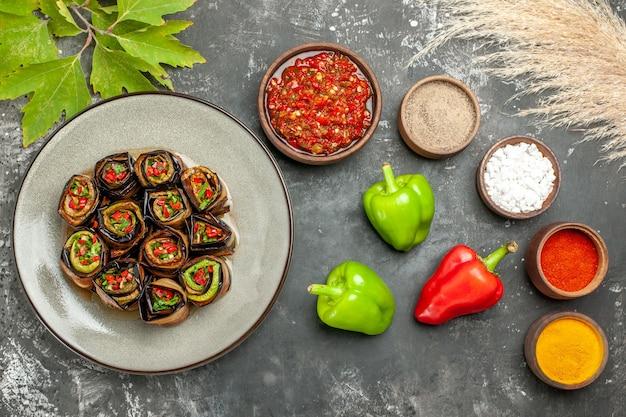 Vista superior rolos de berinjela recheada com especiarias em pequenas tigelas sal pimenta pimenta vermelha açafrão adjika pimentas em fundo cinza