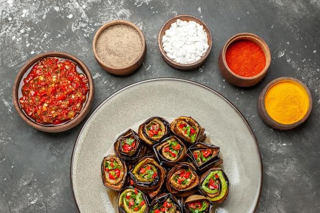 Vista superior rolos de berinjela recheada com especiarias em pequenas tigelas sal pimenta pimenta vermelha cúrcuma adjika em fundo cinza