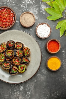 Vista superior rolos de berinjela recheada com especiarias em pequenas tigelas sal pimenta pimenta vermelha cúrcuma adjika na superfície cinza
