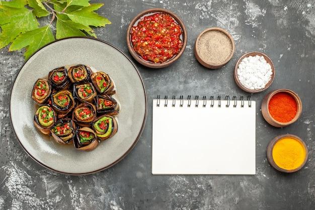 Vista superior rolos de berinjela recheada com especiarias em pequenas tigelas sal pimenta pimenta vermelha cúrcuma adjika um caderno em fundo cinza