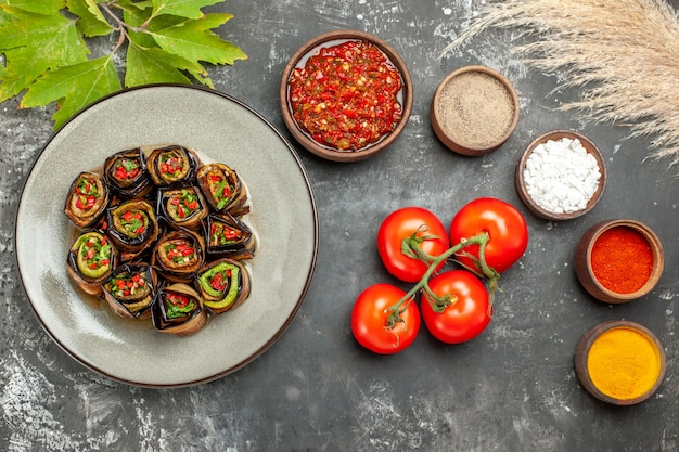 Vista superior rolos de berinjela recheada com especiarias em pequenas tigelas sal pimenta pimenta vermelha cúrcuma tomate adjika em fundo cinza