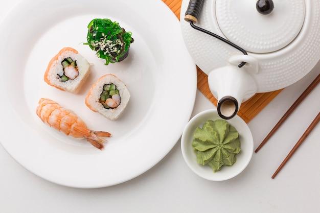 Vista superior rolos de sushi com wasabi em cima da mesa