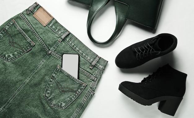 Vista superior, roupas da moda, sapatos, acessórios em um fundo branco. saia jeans, botas pretas, bolsa de couro, smartphone no bolso de trás