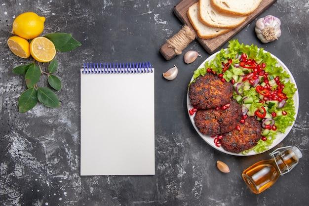 Vista superior saborosa costeleta de carne com salada e pão no fundo cinza prato foto comida refeição