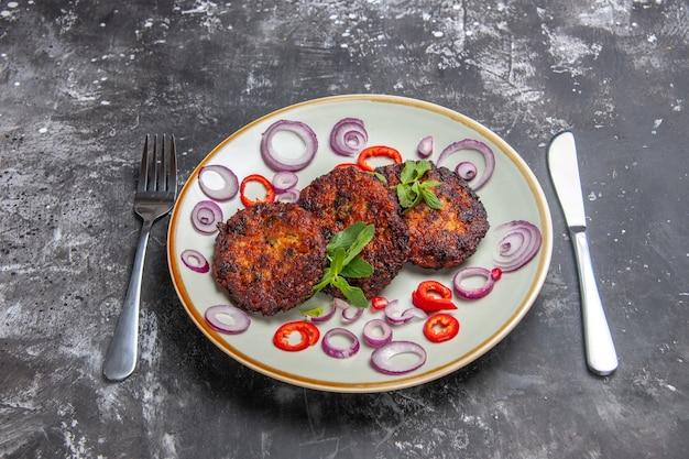 Vista superior saborosa costeletas de carne com anéis de cebola na foto de culinária de refeição de fundo cinza