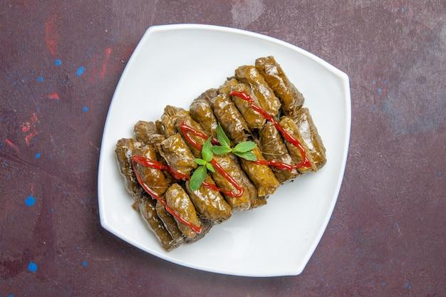Vista superior saborosa folha de prato de carne moída de dolma dentro do prato no escuro