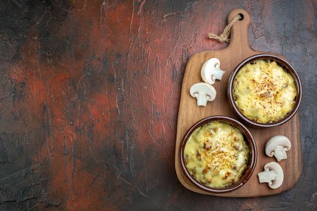 Vista superior saborosa juliana em tigelas recortada cogumelo na tábua de servir de madeira na mesa marrom copia