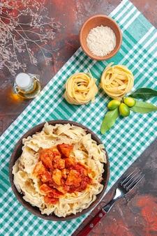Vista superior saborosa massa cozida com frango e molho em comida de massa de superfície escura