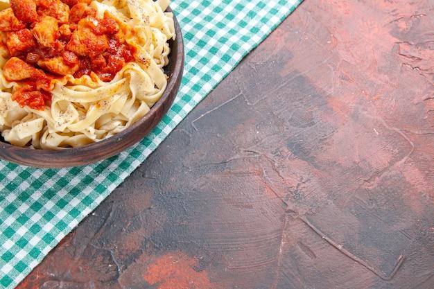 Vista superior saborosa massa cozida com frango e molho em prato de massa com superfície escura