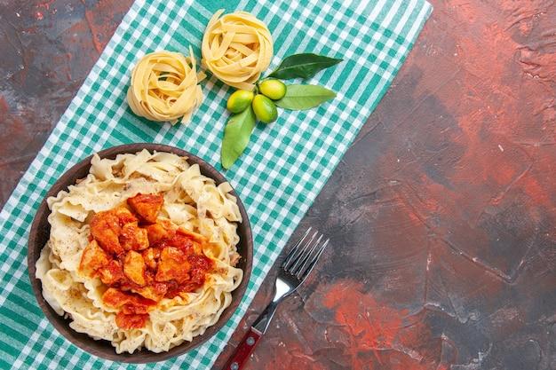 Vista superior saborosa massa cozida com frango e molho em um prato de macarrão de superfície escura
