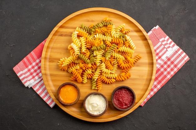 Vista superior saborosa massa italiana incomum massa espiral cozida com temperos no escuro