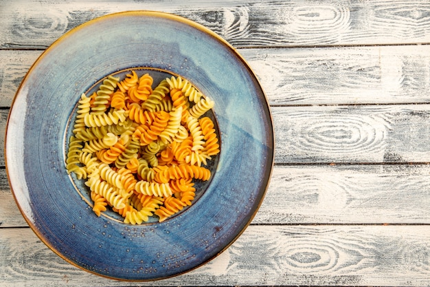 Vista superior saborosa massa italiana incomum massa espiral cozida em madeira cinza