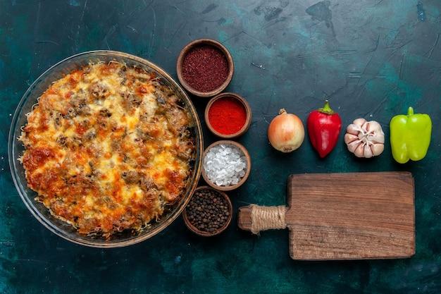 Vista superior saborosa refeição de carne com queijo, assar com vegetais frescos e temperos em mesa azul-escura.